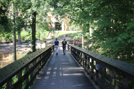 Two people walking across a bridge